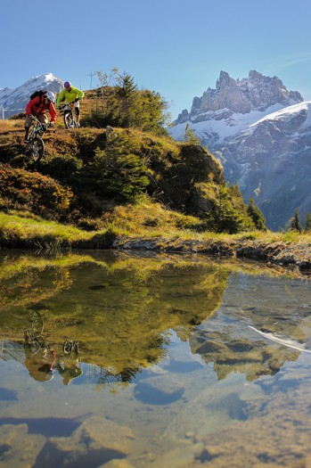 Mountain biking photo of two riders reflected in a lake.