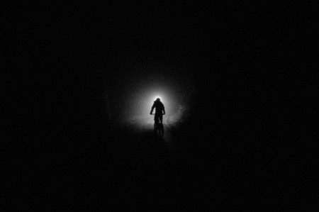 Photo of Stafan Zuercher as he bikes down the mountain in darkness and fog, Haldigrat, Switzerland