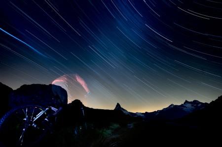 Photograph of a mountain biker riding under the stars in Zermatt