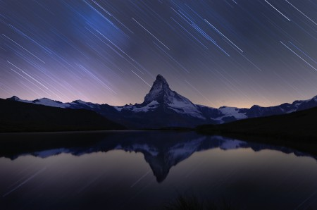 A reflection of the Matterhorn mountain in the lake Stellisee, by night