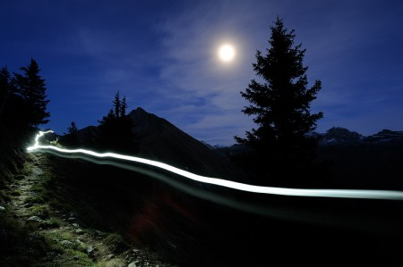 Outdoor photograph of a light trail and the moon.