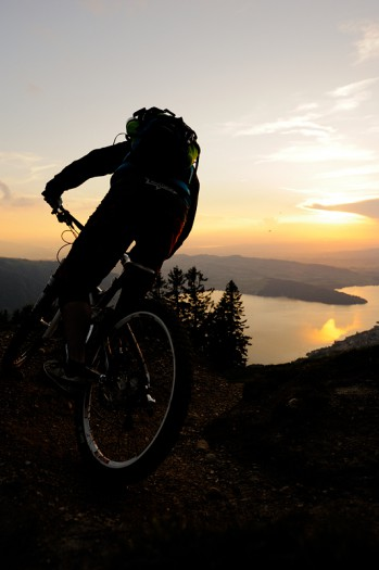 Photo of a mountain biker riding a trail over a lake.