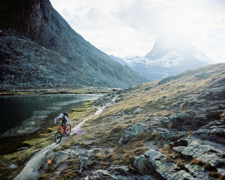 Photograph of Stefan Hellberg riding his mountain bike on a trail by a small lake above Zermatt, Switzerland.