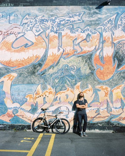 Portrait of fixed gear cyclist leaning against a graffiti wall.